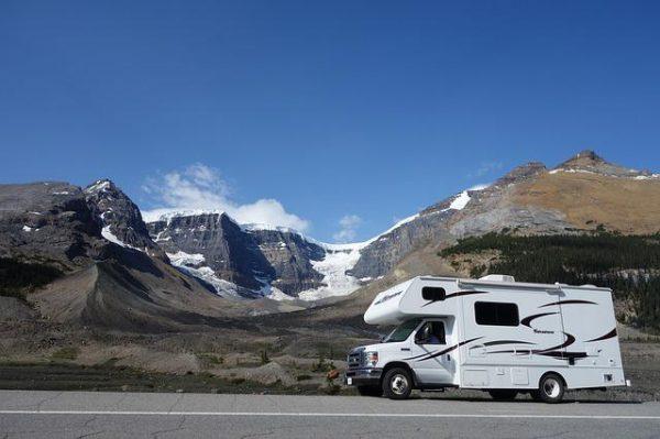 zaparkowany karawan na drodze a w oddali góry miejscami pokryte śniegiem