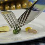 cztery tabletki leżą nabiałym talerzu a jedna z nich jest krojona za pomocą widelca i noża