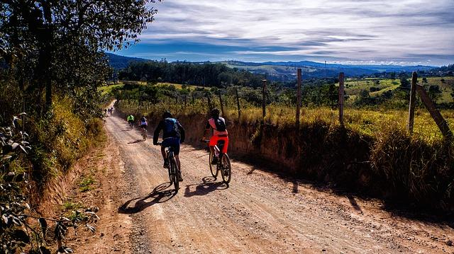 dwie osoby jadą po polnej drodze na rowerach w otoczeniu łąki i gór