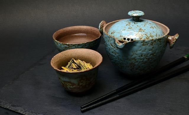 gliniany czajnik z dwoma filiżankami do zaparzania herbaty, w jednej z filiżanek znajduje się susz herbaciany