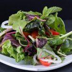 Sałatka z sałaty, cebuli, pomidorów, rukoli i mięty leży na białym talerzu