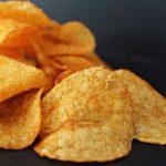 wysypane chipsy leżą na czarnym blacie