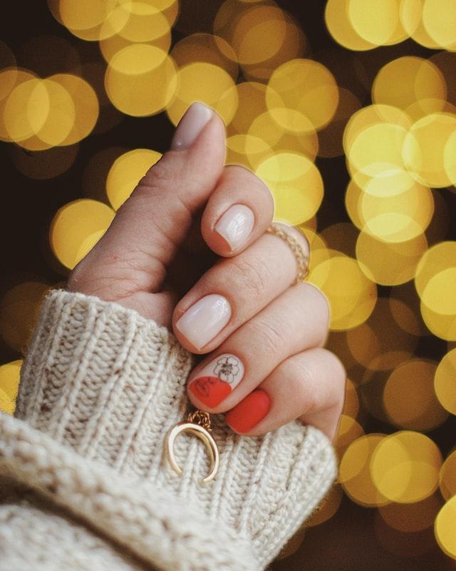 Naturalne i zadbane piękne paznokcie kobiety z namalowanym kwiatkiem