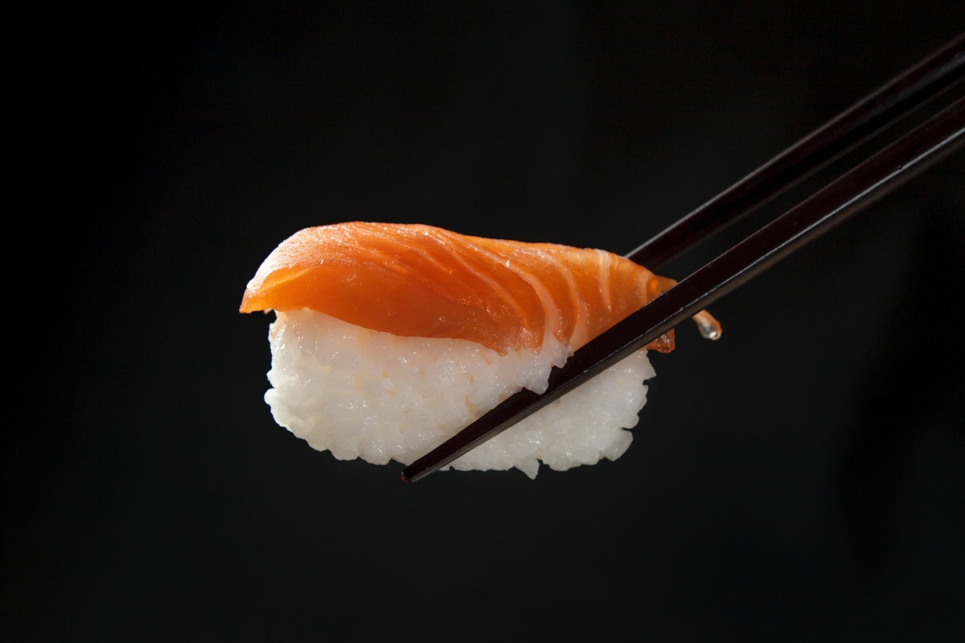 pałeczki trzymają sushi z ryżu i wędzonego łososia
