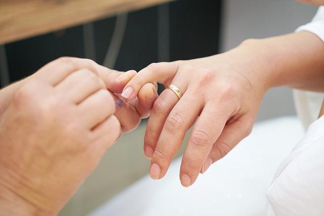 kobieta z obrączką ma pięknie zadbane naturalne paznokcie