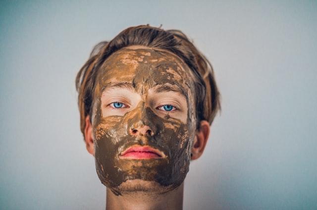 mężczyzna z nałożonym pilingiem kawowym na twarzy