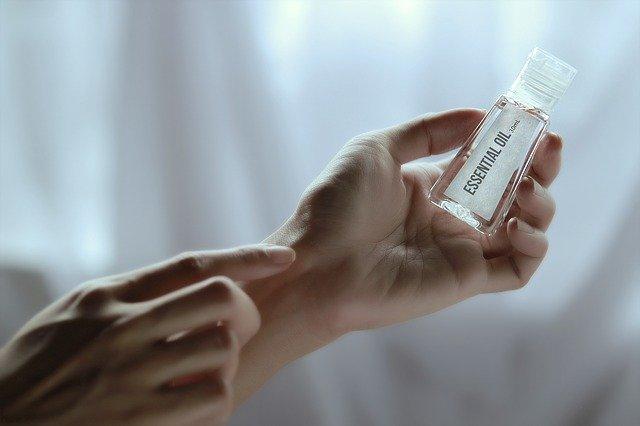 dłoń trzymająca buteleczkę z olejkiem eteryczny