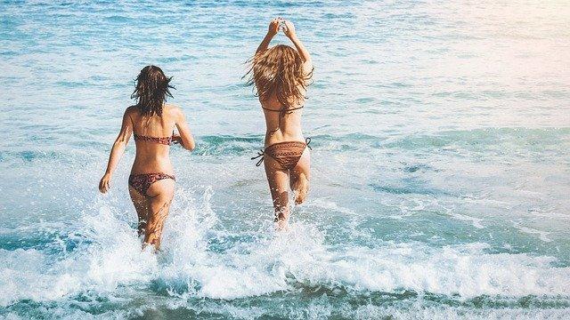 dwie szczupłe kobiety wbiegają do morza