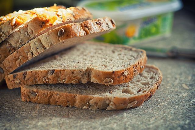 Na blacie leży pokrojony brązowy chleb bezglutenowy z kaszy gryczanej i jaglanej