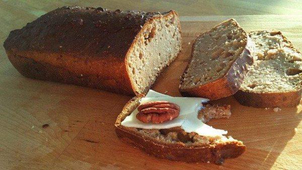 Na drewnianym stole leży pokrojony chleb jaglany bezglutenowy na jednej z 3 kromek jest żółty ser i kawałek orzecha włoskiego