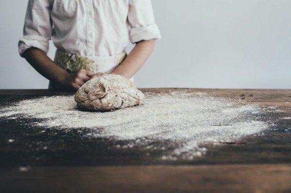 Przed mężczyzną na posypanym mąką stołem leży wyrobione ciasto bezglutenowej kaszy jaglanej