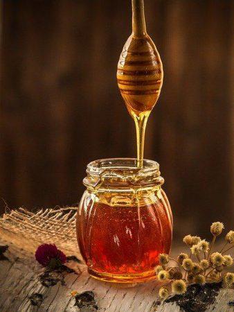 Nieskrystalizowany miód wlewany jest do słoiczka za pomocą drewnianego patyczka do miodów