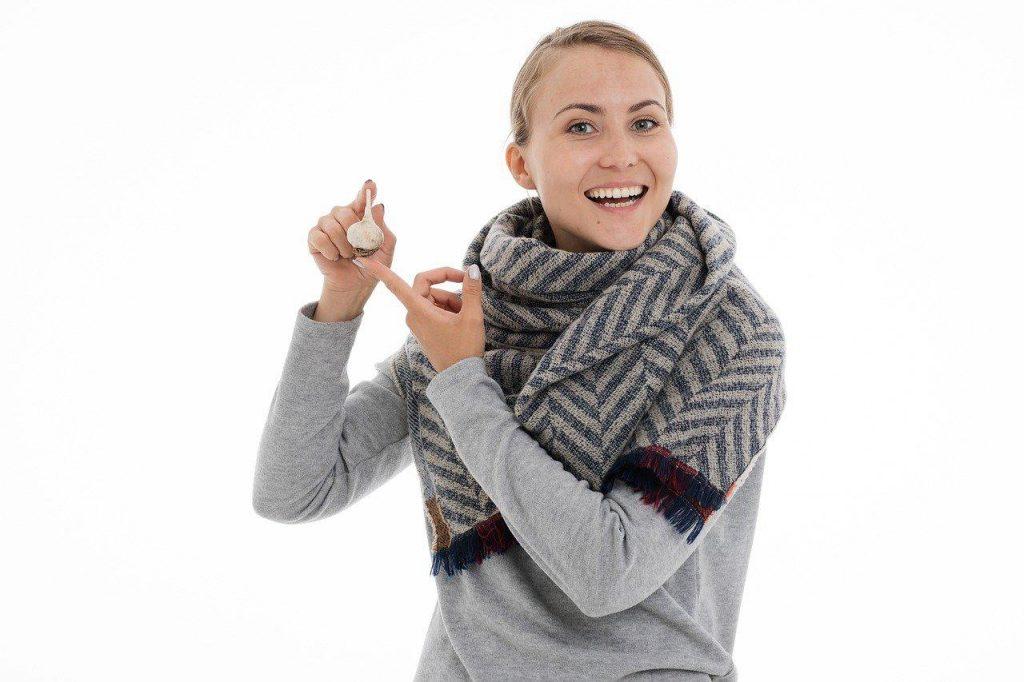 uśmiechnięta kobieta trzyma główkę czosnku