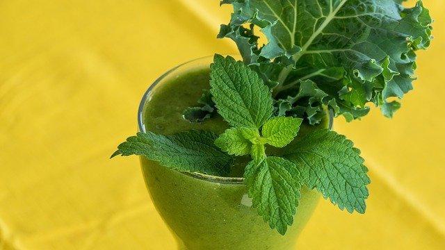 Szklanka zielonego soku z pokrzywy w którym jest zanurzona pokrzywa i liść kapusty