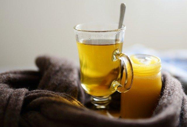 Słoiczek z miodem stoi obok ciepłej herbaty do której dodano łyżeczkę miodu, całość jest otulona szalem