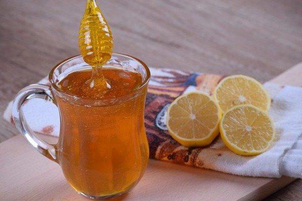 miód wlewany jest do szklanki ciepłej herbaty za pomocą patyczka do miodu obok na szmatce leżą 3 plasterki cytryny