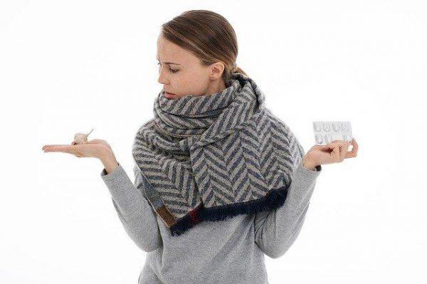 kobieta w jednej dłoni trzyma antybiotyk a w drugiej czosnek