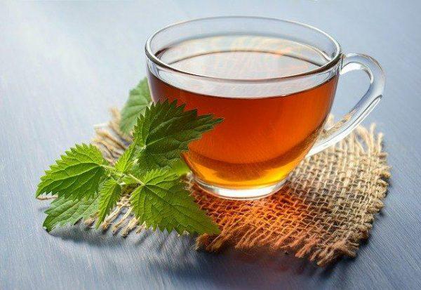 herbata z pokrzywy w filiżance stoi na kawałku materiału a obok leżą listki pokrzywy na cholesterol
