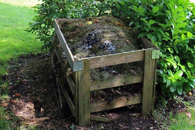 drewniany kompostnik wypełniony ogrodowymi odpadkami