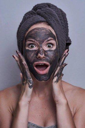 Dziewczyna z zawiniętym ręcznikiem na włosach nakłada czarną maseczkę na twarz przeciwko pryszczom