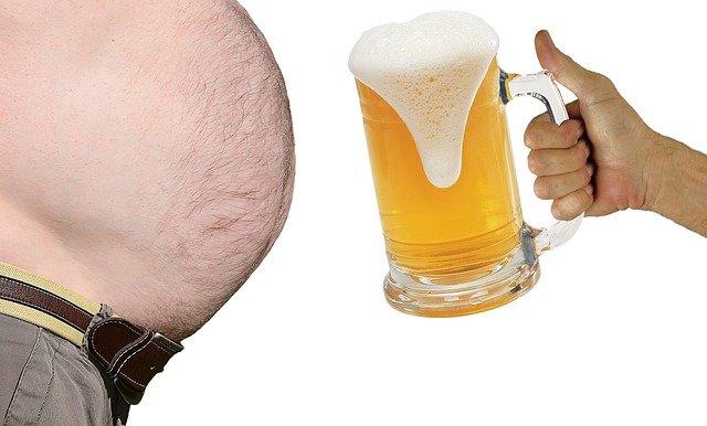 mężczyzna z dużym piwnym brzuchem który zaczyna rosnąć przez picie dużej piwa