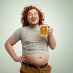 Uśmiechnięty mężczyzna z piwem w ręku ma odsłonięty brzuch piwny