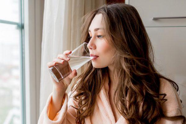ładna kobieta pije wodę bo to skuteczne domowe sposoby na gazy w jelitach