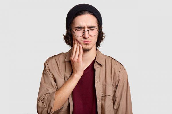 Mężczyzna cierpi na ból zęba, w tym przypadku jest wymagane leczenie kanałowe.