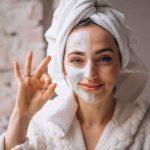 Kobieta z posmarowanym prawym policzkiem usuwa przebarwienia po trądziku