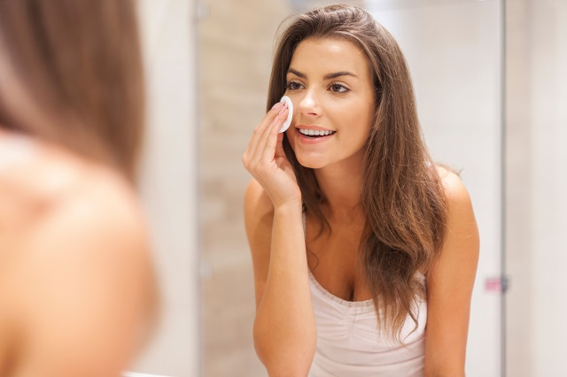 Uśmiechnięta kobieta stosuje domowe sposoby na przebarwienia po trądziku