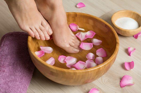 kobieta stosuje domowe sposoby na wrastające paznokcie i moczy stopy w wodzie z solą i płatkami róży