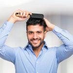 uśmiechnięty mężczyzna czesze swoje przeszczepione włosy