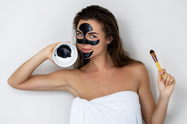 kobieta w ręczniku urzywa maseczki z węgla aktywnego i żelatyny na wągry