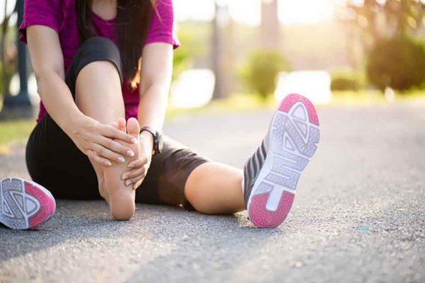 kobieta siedzi na drodze i cierpi z bulu z powodu wrastającego paznokcia