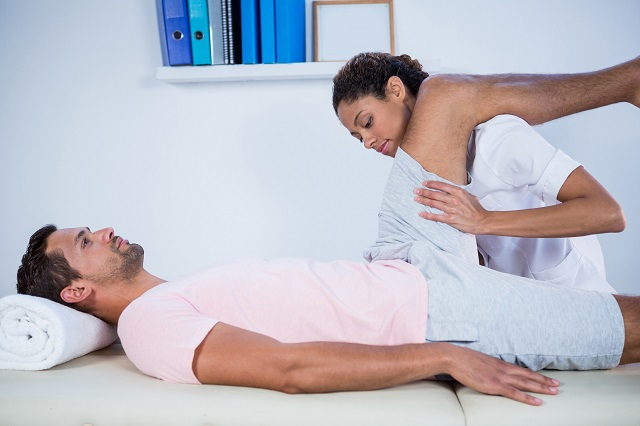 Fizjoterapeutka przeprowadza masaż mięśnia czworogłowego uda u mężczyzny, który ma zaburzenia czucia