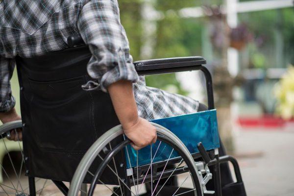 Mężczyzna siedzący na wypożyczonym wózku inwalidzkim