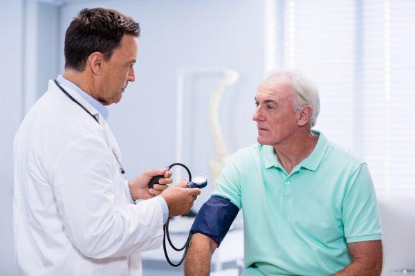 Lekarz mierzy starszemu pany ciśnienie krwi za pomocą ciśnieniomierza