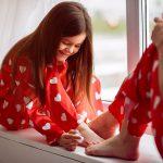 Dziewczynka wraz z mamą maluje sobie paznokcie u nóg zakrywając białe plamki