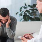 Mężczyzna cierpiący na bóle głowy omawia swoje dolegliwości z lekarzem
