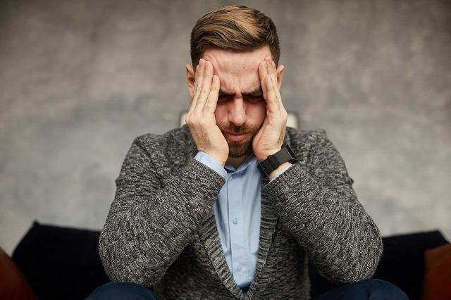Mężczyzna w momencie zmagający się z bólem głowy spowodowanym przez zapalenie zatok