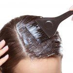 Kobieta za pomocą pędzla nakłada maskę z drożdży na włosy