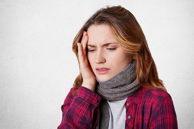 Kobieta cierpiąca na silny ból głowy przy kaszlu
