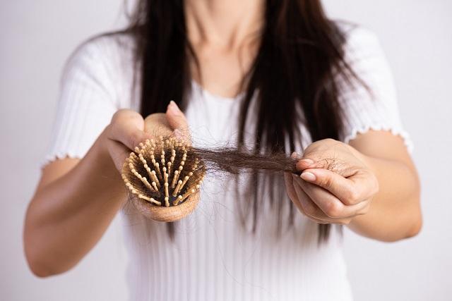 Szczotka do włosów, na której znajdują się wypadające włosy, aby tego uniknąć należy stosować drożdże na włosy