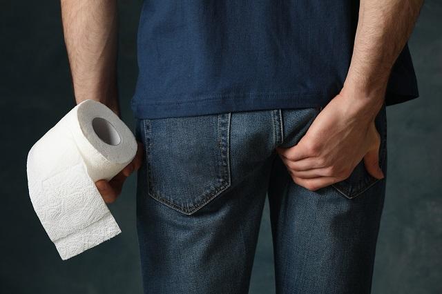 Mężczyzna cierpiący na ból w okolicy odbytu udaje się do toalety