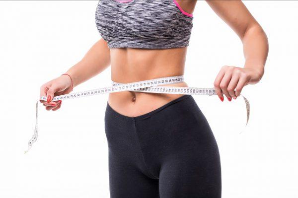 Kobieta mierzy obwód brzucha, ponieważ korzystając z diety optymalnej dr Kwaśniewskiego schudła kilka kilogramów.