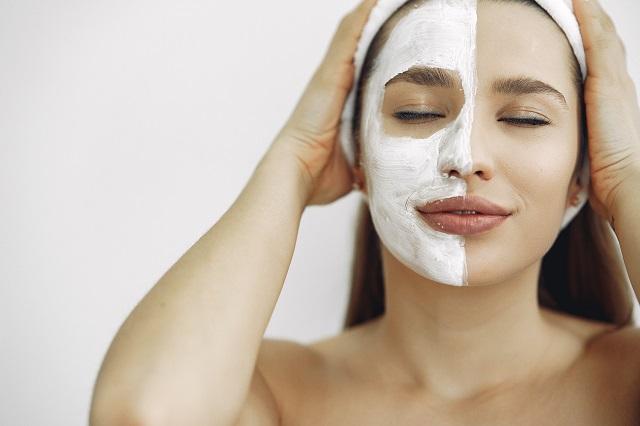 Kobieta stosująca krem do twarzy z witaminą e
