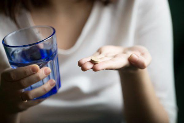 Kobieta biorąca tabletki antykoncepcyjne na przyśpieszenie okresu.