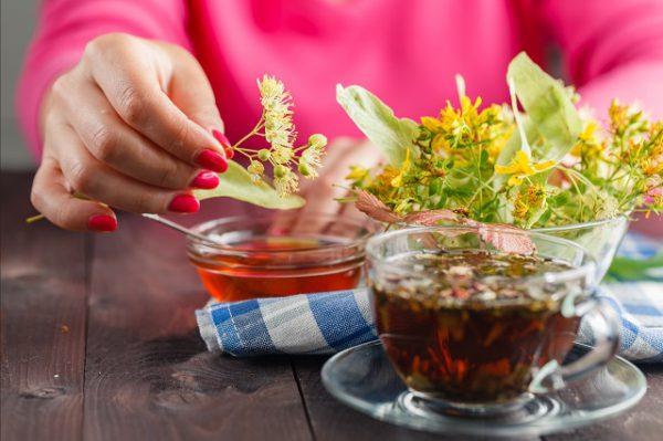 Kobieta w ciąży przygotowuje herbatę z kwiatu lipy